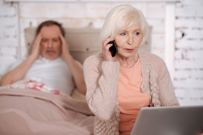 senior women calling emergency while sitting on bed